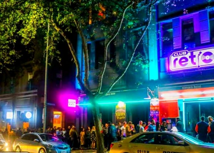 street view from 383 lonsdale street of brightly neon lit club retro night club at night with large crowd lining up and cars parked on road