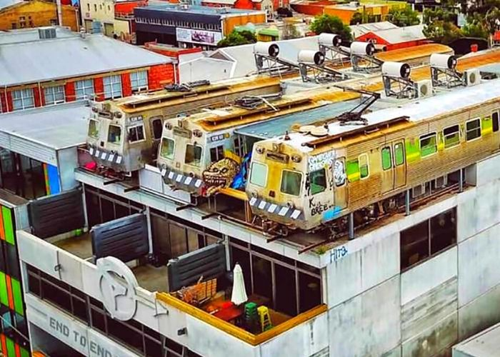 three trains on top of building in collingwood forming easeys rooftop bar  with grafiti