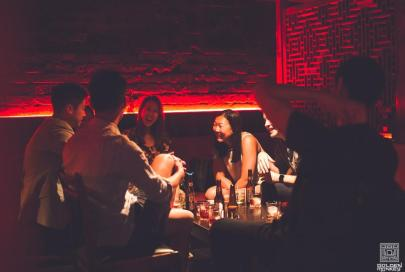 friends drinking in booth at basement nightclub