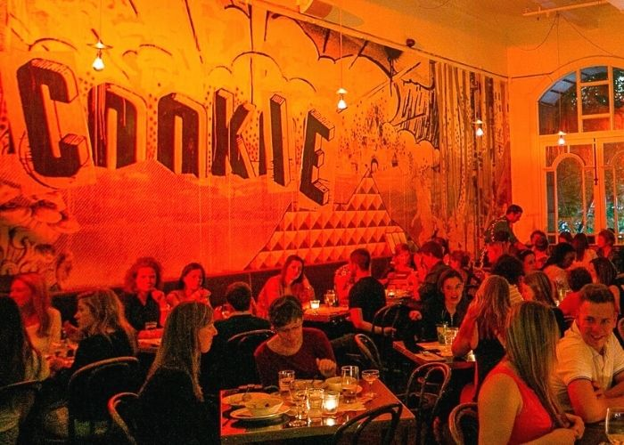 inside bustling restaurant venue Cookie with people seated drinking and eating dinner