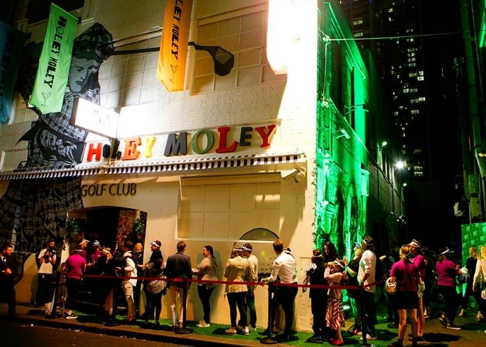 outside vie of holey moley golf club on little bourke street in melbourne cbd with large line up of people at night