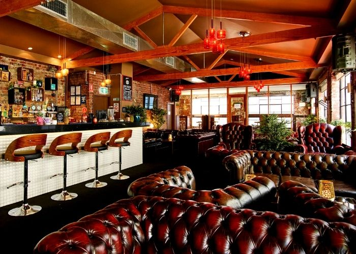 decadent brown leather couches and bar stools lining la la land bar with exposed timber beams and outdoor smoking balcony