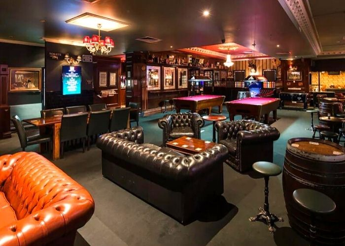 dark leather couches and two red velvet pool tables in English styled pub, the lion hotel in Melbourne central on La Trobe Street