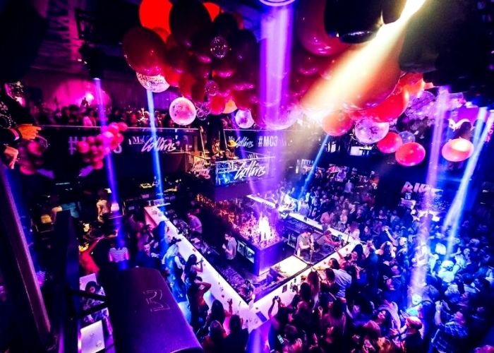Huge party at main bar in Ms Collins night club with coloured wash lights and balloons and DJ