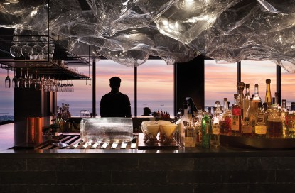 Rooftop bar with man looking out window at sunset ocean view