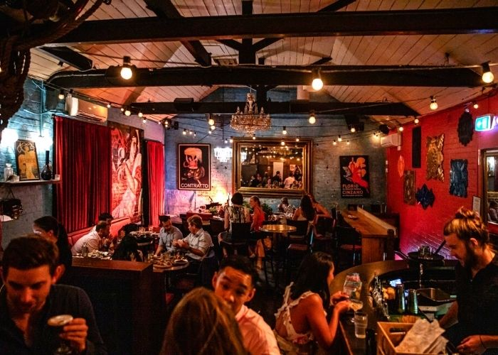 crowd talking inside murmur piano bar with exposed wooden beams in decadent club with red furnishings