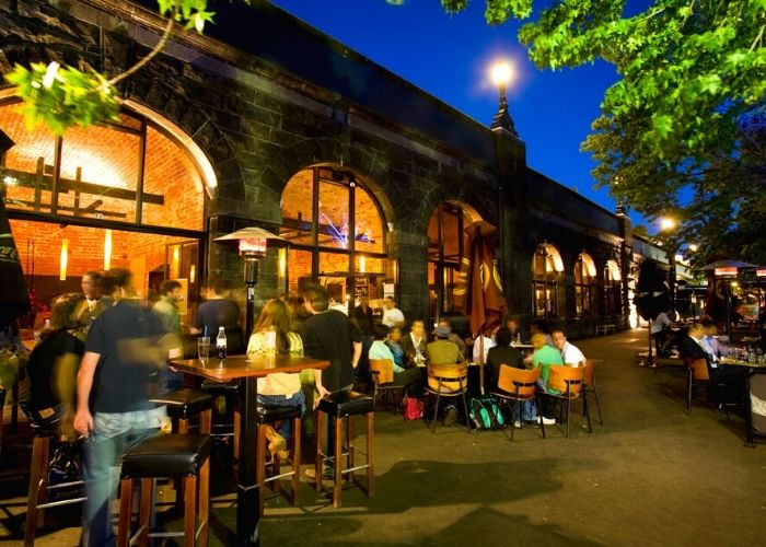 people dining outdoors at night at riverland beer garden on yarra river outside of federation wharf vaults