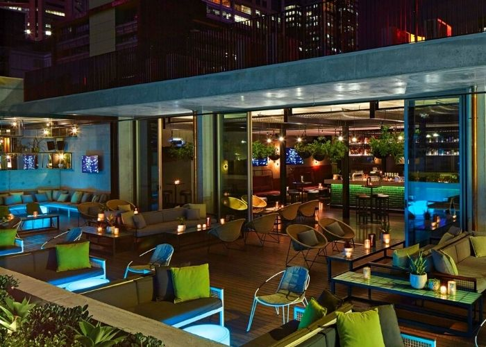 glowing melbourne cbd views from rooftop at QT with chairs lounges and green cushions