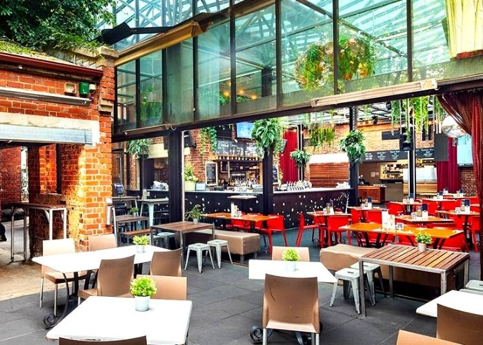 tables and chairs in the royal melbourne hotels glass atrium with hanging plants