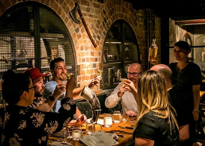 group of adults toasting drinks at valhalla underground bar with bring arches and viking axe in background