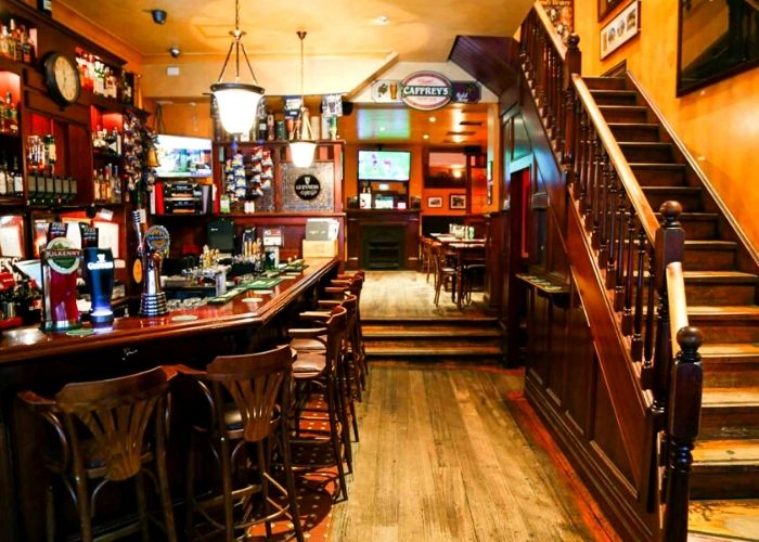interior of old timber bar and wooden staircase inside the Irish times pub on 427 Little Collins Street