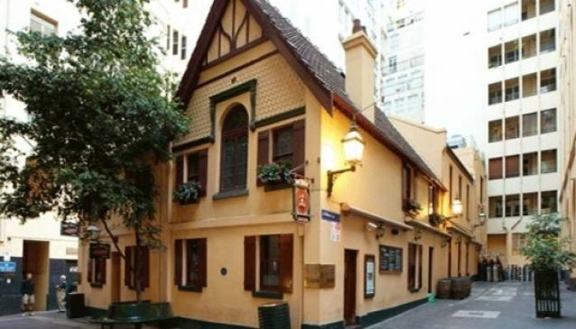street view of yellow restored pub the mitre tavern on bank place with trees on footpath