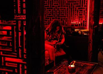 woman seated at booth with wooden screens and red light of club