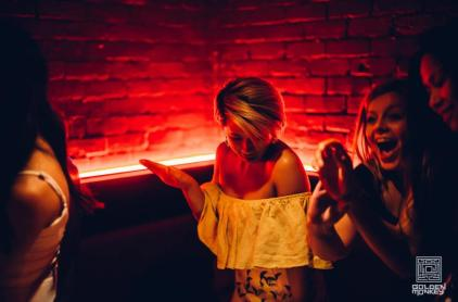 women laughing and woman in yellow dress dancing at bar with red neon light