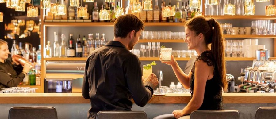 man and woman on a date at a bar drinking cocktails with female bartender shaking martini's