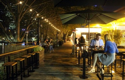 man an woman drinking wine at outdoor arbour bar on melbourne yarra river at night