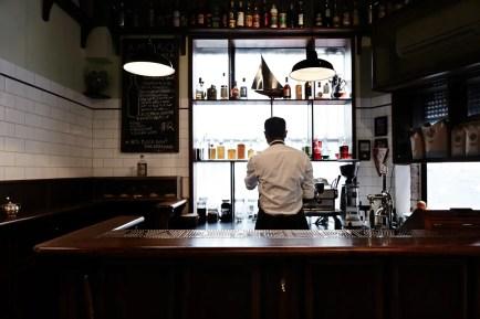 inside melbourne hidden bar americano. back of bar tender making drinks with wooden bench and overhanging lights