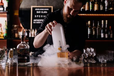 male bar tender with beard unveiling dry ice cocktail on wooden bar at clara