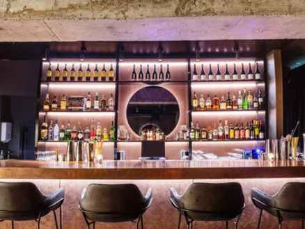 sleek modern designed bar at clara with round mirror and wine bottles and four black leather bar stools