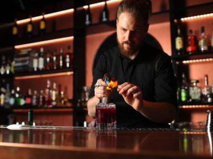 bar tender adding rosemary to cocktail with drinks in shelves behind him
