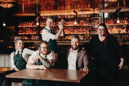 five bar staff smiling at Melbourne bar wearing aprons