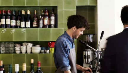 male barista in apron making coffee at kirks with wine bottles on shelves