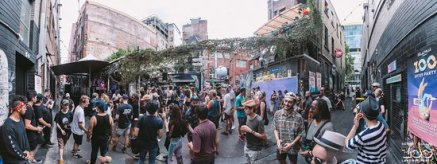 crowds partying in melbouren laneway music festival with brick buildings in background