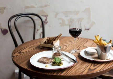 circular table with one chair, toast, chips and a glass of red wine