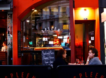 two street diners drinking wine with spleen happy hour sign