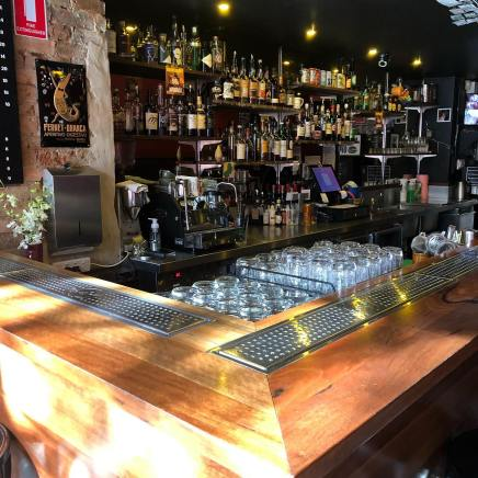 corner of wooden bar with glasses beer taps and wine