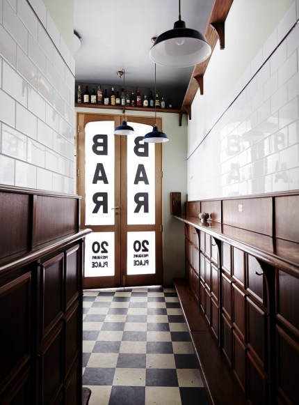 inside 1920's themed bar americano with french doors, wine bottles and white downlights and tiles
