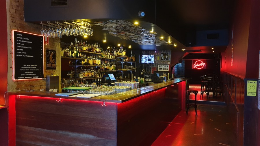 fully stocked bar with wine spirts and tab beer with red neon spleen bar sign