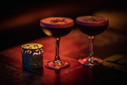 two experesso martini cocktails in glasses on table with candle