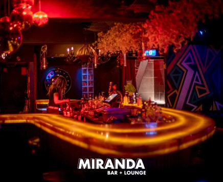 yellow counter top of miranda bar with female staff making drinks