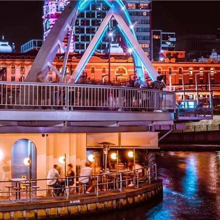 curved evan walker bridge over ponyfish restaurant with flinders street station in background