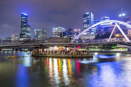 melbourne city lights reflection off yarra river with ponyfish bar under pedestrian bridge