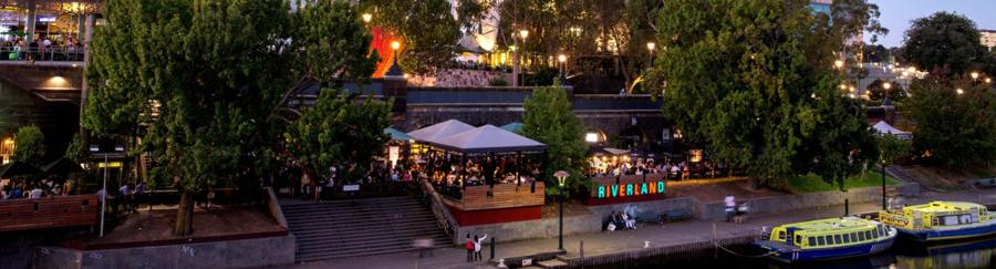 aerial view of Riverland bar at night from above the yarra river with bots and patrons drinking under trees in CBD