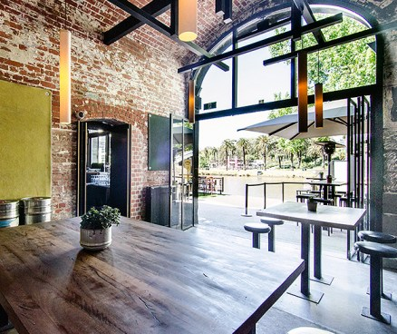 brick walls and exposed roof beams inside federation wharf vaults of melbournes riverland bar