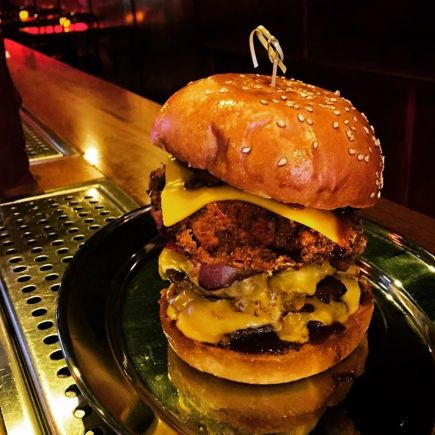 large triple cheese burger on stainless steel bar counter