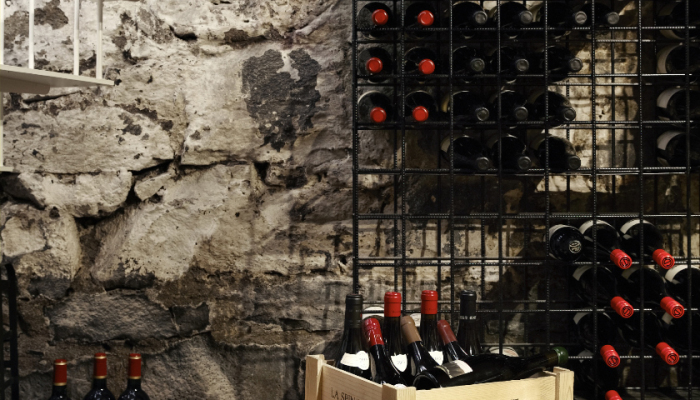dark wine cellar with rock wall and black bottles of wine with red lids