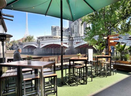 view from riverland bar over looking tables and chairs with yarra river and princess bridge in the back ground