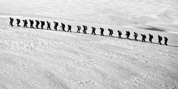 line of backpackers in the snow