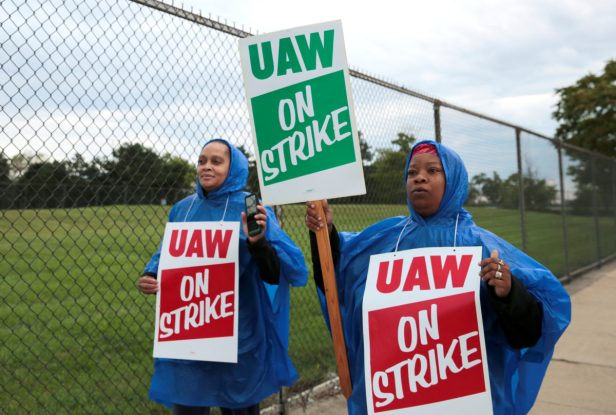 United Auto Workers, Aramark workers carry strike signs while picketing outside the General Motors Detroit-Hamtramck assembly plant in Detroit,