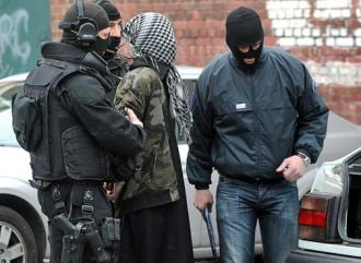 French police make an arrest during the spreading tide of raids
