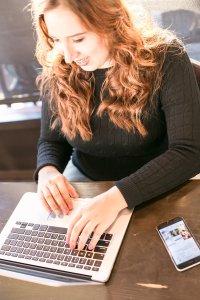 Nicole working at a laptop, she has long, auburn hair.