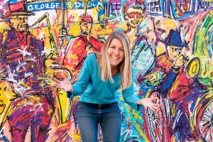 Sally in front of a wall mural. She is bending slightly and has her hands outstretched in a welcoming and excited motion.