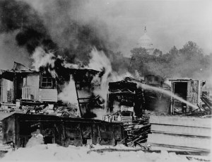 Shacks, put up by the Bonus Army on the Anacostia flats, Washington, D.C., burning after the battle with the military. The Capitol in the background. 1932.