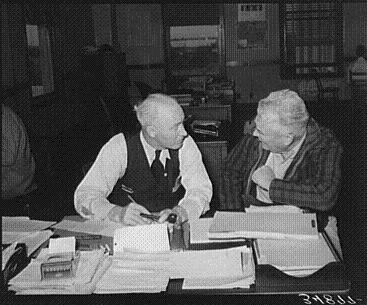 A lively discussion between a worker and his client over lots of paperwork.