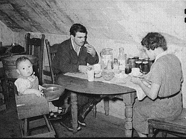 A young family eating together in cramped housing conditions, a common site for social workers in the Great Depression era.