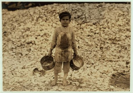 Manuel, the young shrimp-picker, five years old, and a mountain of child-labor oyster shells behind him. He worked last year. Understands not a word of English. Dunbar, Lopez, Dukate Company. Location: Biloxi, Mississippi. 1911 February. Hine, Lewis 1874-1940, photographer. (LC-DIG-nclc-00828). Library of Congress Prints and Photographs Division Washington, D.C.